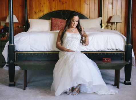 Pretty Wedding Dress Bride getting ready on bed at Wonser Woods Estate